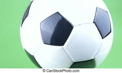 Soccer ball spinning on a green background.