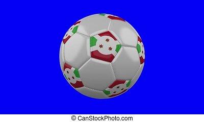 Soccer ball with Burundi flag rotates on blue chroma key background, loop