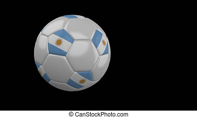 Soccer ball with flag of Argentina flies past camera, slow motion, alpha channel