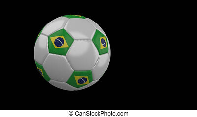 Soccer ball with flag of Brazil flies past camera, slow...