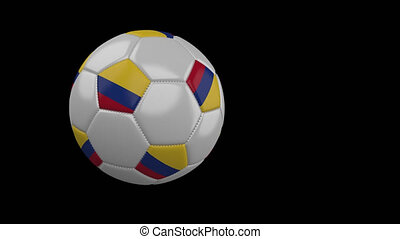Soccer ball with flag of Colombia flies past camera, slow motion, alpha channel