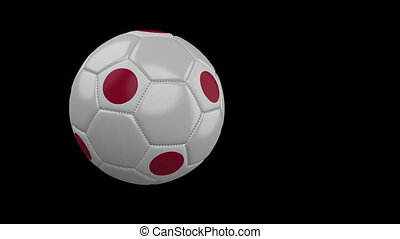 Soccer ball with flag of Japan flies past camera, slow motion, alpha channel