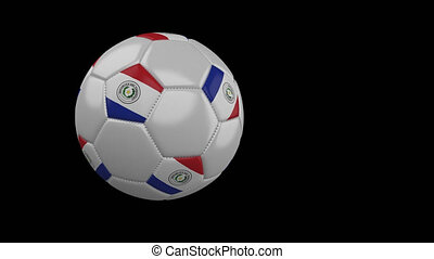 Soccer ball with flag of Paraguay flies past camera, slow motion, alpha channel