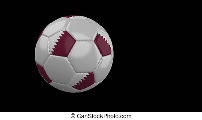Soccer ball with flag of Qatar flies past camera, slow motion, alpha channel