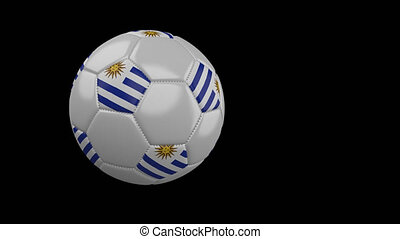 Soccer ball with flag of Uruguay flies past camera, slow...
