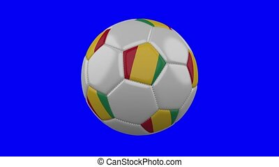 Soccer ball with Guinea flag on blue chroma key background, loop