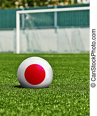 Soccer Ball with Japan Flag on the grass in stadium
