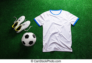 Soccer ball,cleats and white t-shirt against artificial turf...
