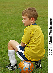 soccer boy - boy waiting on sidelines during a soccer game