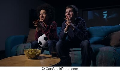 Soccer fan teens emotionally watching match on TV