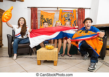 Soccer Fans Cheering While Watching Match At Home
