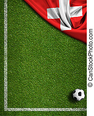 Soccer field with ball and flag of Switzerland