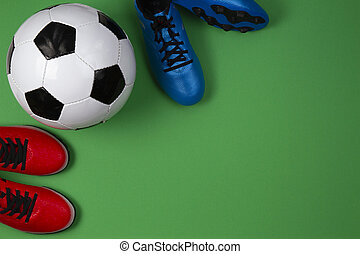 Soccer football sport background. Top view to soccer ball and boots on green background