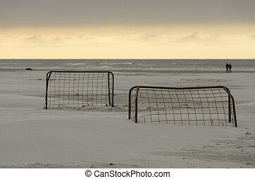 Soccer goals on a beach at sunset