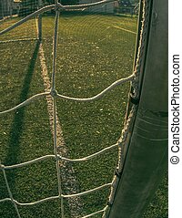 Soccer green field viewed through white square gate net.