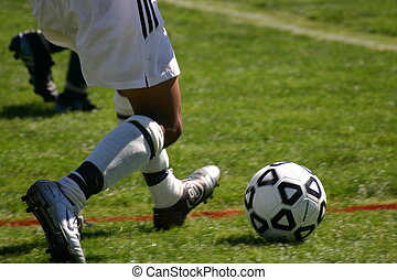 Soccer Kick - Soccer player about to kick the ball to keep...