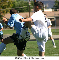 Soccer Kick - Soccer players collide while trying to bring...