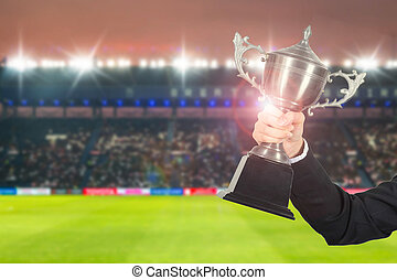 Soccer manager team holding trophy champions in the stadium.