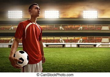 Soccer player holding soccer ball