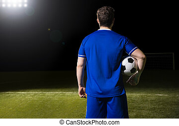 Soccer player in blue jersey on stadium