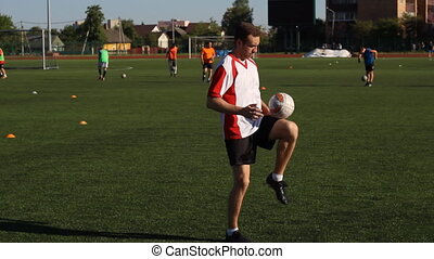 Soccer player is training and bouncing a soccer ball by his foot