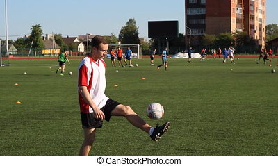 Soccer player is training and bouncing a soccer ball on his foot