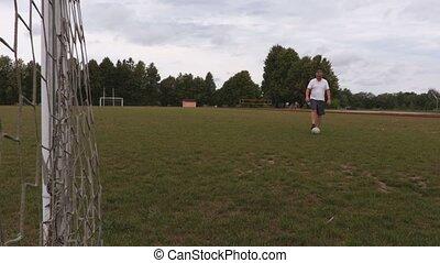 Soccer player juggles ball in football goal