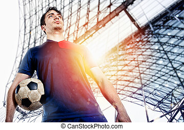 Soccer player ready to play with soccerball at the stadium
