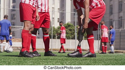 Soccer player remove its prosthetic leg - Side view mid ...