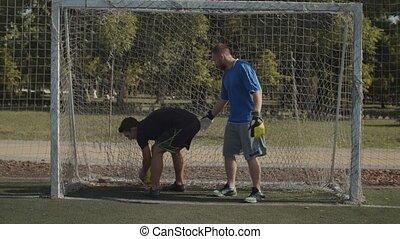 Soccer player scoring a goal during football match