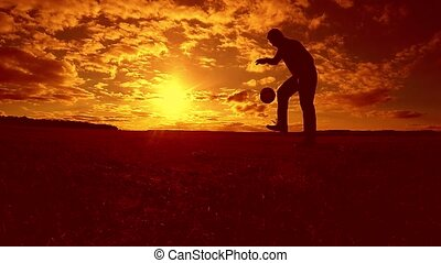 soccer player stuffing ball silhouette man kicks ball in...