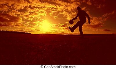 soccer player stuffing ball silhouette man kicks ball in the...