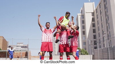 Soccer players celebrating on field - Front view of a multi-...