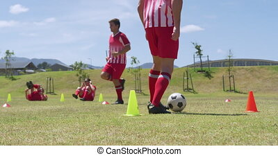 Soccer players exercising on field - Side view low angle of ...