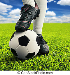 Soccer player's feet in casual pose on an open playing field, with sky in background