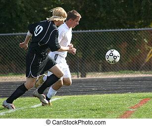Soccer Players - Soccer players run toward the ball