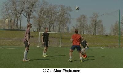 Soccer players training football in the pitch