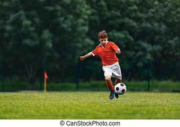 Soccer shooting. Boy kicking soccer ball on grass field. Young football player in action running jumping, and shooting the ball. Junior level sports competition. Footballer in red jersey shirt