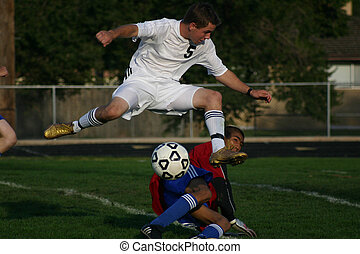 Soccer player leaps over goalkeeper to take shot on goal