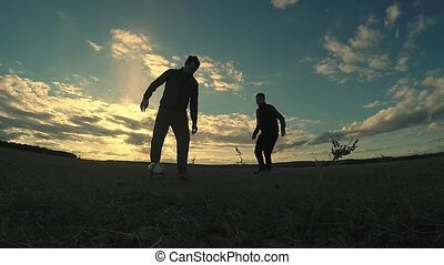 soccer. sky two men play soccer the beautiful silhouettes...