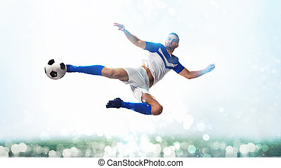Soccer striker hits the ball with an acrobatic kick in the air on white background