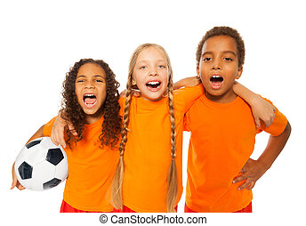 Happy laughing and screaming soccer team of boy and girls holding football ball hugging