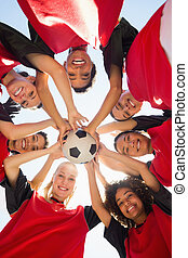 Soccer team with ball forming huddle against sky - Directly ...