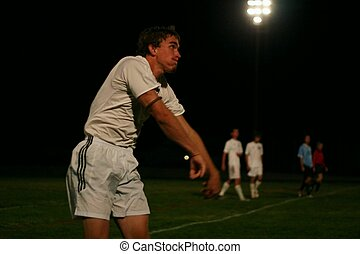 Soccer Throw - Soccer player throwing ball back onto the...