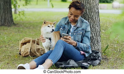 Sociable girl is using smartphone texting friends and...