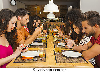 Social but not social - Group of friends at a restaurant...