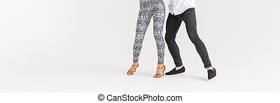 Social dance, bachata, kizomba, zouk, tango concept - Close-up of man's and woman's legs while dancing over white background with copy space