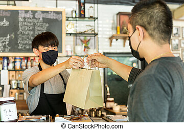 Social distance conceptual waiter giving takeaway bag to customer at cafe