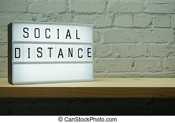 Social Distance word in light box on wooden shelve and white...