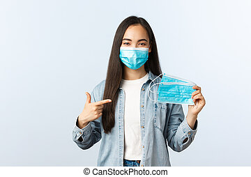 Social distancing lifestyle, covid-19 pandemic everyday life and leisure concept. Cute friendly asian girl showing medical mask and explain improtance of wearing it during coronavirus outbreak